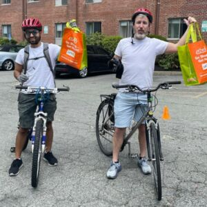 Two people on bikes with trash bags